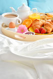 Breakfast tray in bed in hotel room Royalty Free Stock Photography