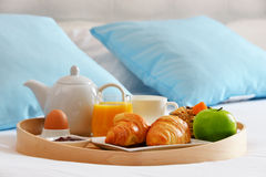 Breakfast on tray in bed in hotel room Royalty Free Stock Photos