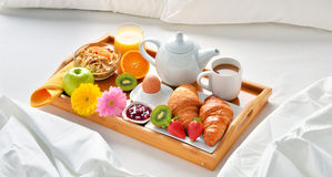 Breakfast tray in bed in hotel room Stock Photos