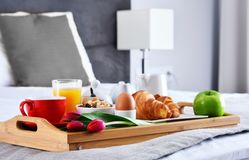Breakfast on tray in bed in hotel room.  Stock Photos