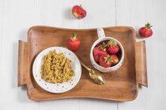 Breakfast on a tray, buckwheat porridge and ripe red strawberry. A useful breakfast on a tray, buckwheat porridge and ripe red strawberries in a cup on a light Royalty Free Stock Photo