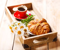 Breakfast tray with croissants, cup of coffee and daisy flowers Stock Photo