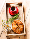 Breakfast tray with croissants, cup of coffee and daisy flowers Stock Photography