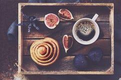 Breakfast tray - cup of espresso, cinnamon bun and fresh figs. Breakfast tray - cup of espresso, homemade cinnamon bun and fresh figs, table top view Stock Photo