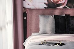 Breakfast tray on grey bed with black cushion in pink bedroom in. Terior with drapes. Real photo with focus on the tray concept concept stock images
