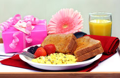 Breakfast Tray for Mom. Breakfast of eggs, toast, fresh fruit and orange juice on a breakfast tray.  A gift and beautiful flower all for Mom Stock Image