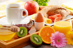 Breakfast on tray served with coffee, juice, egg, and rolls Stock Image