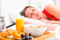 Breakfast on a tray and sleeping girl Royalty Free Stock Photography