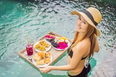 Breakfast tray in swimming pool, floating breakfast in luxury hotel. Girl relaxing in the pool drinking smoothies and stock photo
