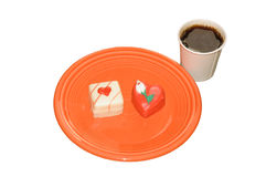 Breakfast treats. Valentines treats on an orange plate with a paper cup full of coffee on a white background Stock Images