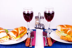 Breakfast for two. Two delicious sandiches on plate with two glasses of wine Stock Images