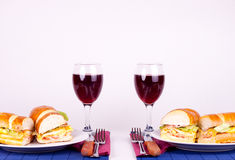 Breakfast for two. Two delicious sandiches on plate with two glasses of wine Royalty Free Stock Photos
