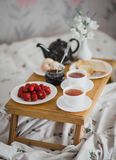 Breakfast for two in bed. Two cups of tea, strawberries, jam, toasts and eggs on a tray in bed Stock Photo