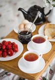 Breakfast for two in bed. Two cups of tea, strawberries, jam, toasts and eggs on a tray in bed Stock Photography