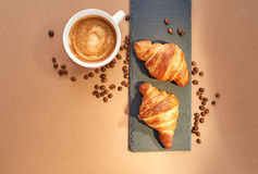 Breakfast of two French croissants with coffee. Flat composition of two croissants with cup of coffee and coffee beans on brown craft paper background Royalty Free Stock Images