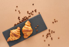 Breakfast of two French croissants. Flat composition of two croissants with coffee beans on brown craft paper background Stock Image