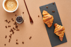 Breakfast of two French croissants with jam and coffee. Flat composition of two croissants with cup of coffee, jam and wooden spoon on brown craft paper Royalty Free Stock Images