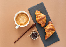 Breakfast of two French croissants with jam and coffee. Flat composition of two croissants with cup of coffee, jam and wooden spoon on brown craft paper Stock Photo