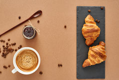 Breakfast of two French croissants with jam and coffee. Flat composition of two croissants with cup of coffee, jam and wooden spoon on brown craft paper Royalty Free Stock Photo