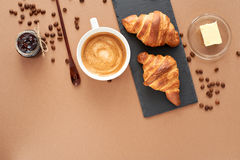 Breakfast of two French croissants with jam and coffee. Flat composition of two croissants with cup of coffee, jam and wooden spoon on brown craft paper Stock Images