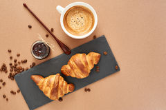 Breakfast of two French croissants with jam and coffee. Flat composition of two croissants with cup of coffee, jam and wooden spoon on brown craft paper Stock Photography