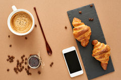 Breakfast of two French croissants with jam and coffee. Flat composition of two croissants with cup of coffee, jam and wooden spoon on brown craft paper Stock Image