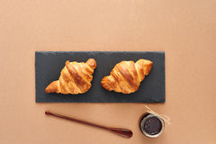 Breakfast of two French croissants with jam. Flat composition of two croissants with jam and wooden spoon on brown craft paper background Stock Photos