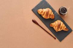 Breakfast of two French croissants with jam. Flat composition of two croissants with jam and wooden spoon on brown craft paper background Royalty Free Stock Images
