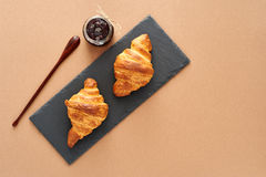 Breakfast of two French croissants with jam. Flat composition of two croissants with jam and wooden spoon on brown craft paper background Royalty Free Stock Image