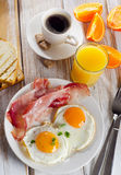 Breakfast with two fried eggs, bacon,toasts  and coffee. Royalty Free Stock Photography