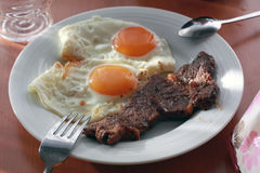 Breakfast with two fried eggs and meat steak. Stock Photos