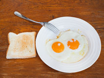 Breakfast with two fried eggs in white plate Royalty Free Stock Photos