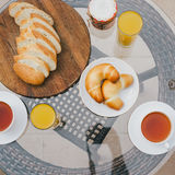 Breakfast for two persons on a balcony with beautiful view. On the ocean. Fresh tea, juice, croissants, jam and bread Stock Images