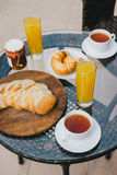 Breakfast for two persons on a balcony with beautiful view. On the ocean. Fresh tea, juice, croissants, jam and bread Royalty Free Stock Image