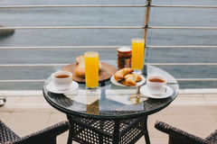 Breakfast for two persons on a balcony with beautiful view. On the ocean. Fresh tea, juice, croissants, jam and bread Stock Photography