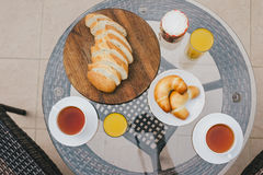 Breakfast for two persons on a balcony with beautiful view. On the ocean. Fresh tea, juice, croissants, jam and bread Stock Image