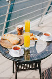 Breakfast for two persons on a balcony with beautiful view. On the ocean. Fresh tea, juice, croissants, jam and bread Royalty Free Stock Photos