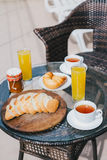 Breakfast for two persons on a balcony with beautiful view on the ocean. Fresh tea, juice, croissants, jam and bread Stock Images