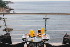 Breakfast for two persons on a balcony with beautiful view on the ocean. Fresh tea, juice, croissants, jam and bread Royalty Free Stock Image