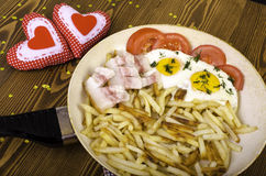 Breakfast for two on Valentine's Day. Frying pan with a meal and Royalty Free Stock Photo