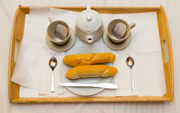 Breakfast for two on a wooden tray are two cups teapot baguettes on fresh crispy plates Royalty Free Stock Images