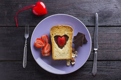Breakfast by Valentine's Day with chocolate, strawberry, nuts an. D red ceramic heart on a brown wooden table Royalty Free Stock Image