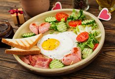 Breakfast on Valentine`s Day - fried egg in the shape of a heart, toasts, sausage, bacon and fresh vegetables Stock Image
