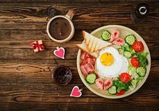 Breakfast on Valentine`s Day - fried egg in the shape of a heart, toasts, sausage, bacon and fresh vegetables Royalty Free Stock Photography
