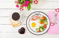 Breakfast on Valentine`s Day - fried egg in the shape of a heart, toasts, sausage and fresh vegetables. Cup of coffee. English breakfast. Top view royalty free stock images
