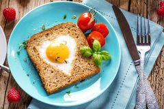 Breakfast on Valentine`s Day - fried eggs and bread in the shape of a heart and fresh vegetables royalty free stock image