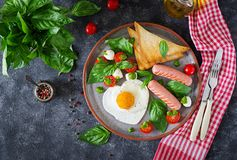 Breakfast on Valentine`s Day - fried eggs in the shape heart, sausage, toast and caprese salad. Of a tomato, basil and mozzarella. Homemade, tasty food. Top royalty free stock photo
