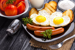 Breakfast on Valentine`s Day - fried eggs in the shape of a heart and sausages. Stock Photography