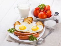 Breakfast on Valentine`s Day - fried eggs in the shape of a heart and sausages. Royalty Free Stock Photos