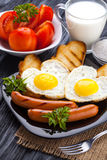 Breakfast on Valentine`s Day - fried eggs in the shape of a heart and sausages. Top view Stock Photography
